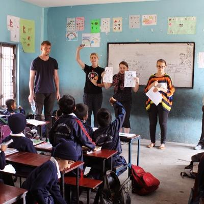 A group of Childcare volunteers team up to help children learn about good dental hygiene in Nepal, Asia.